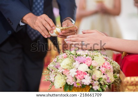 elder hands pouring blessing water into hand of bride in Thai culture wedding ceremony