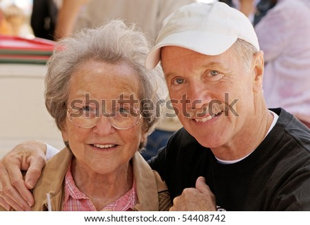 Elder lady enjoying the company of her mature son at a taco stand