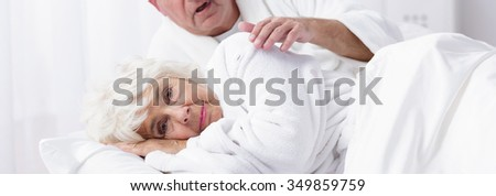 Elder lady is lying on the bed