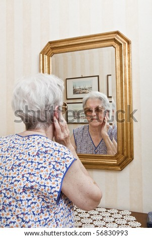 elder lady pensive at the mirror - stock photo