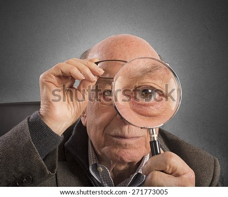Elder magnifies and tries with magnifying glass - stock photo