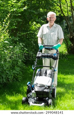 Elder man cutting grass with lawn mower - stock photo