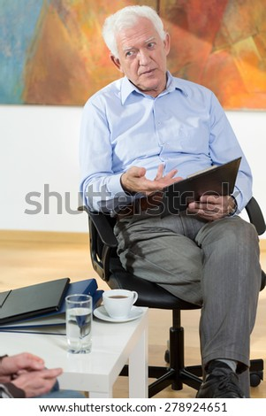 Elder man doing business at home, vertical - stock photo
