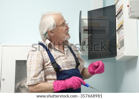 Elder man fixing an electric meter in pink gloves - stock photo