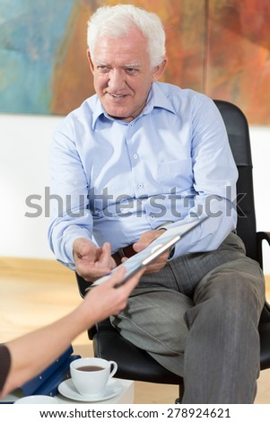 Elder man having business meeting at home - stock photo