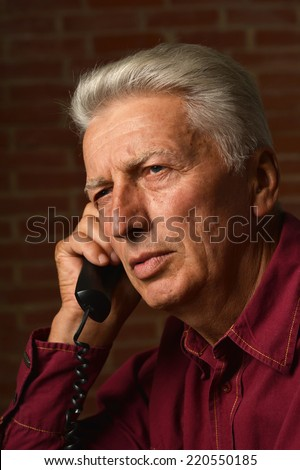 Elder man in a shirt on a brick background - stock photo