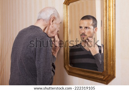 elder man looking a younger himself in the mirror