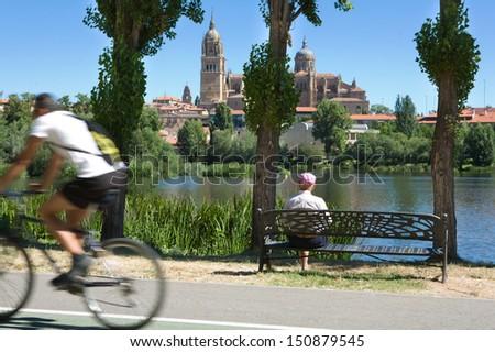 Elder man on bench during walk beside the river, Salamanca - stock photo