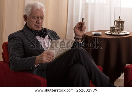Elder man reading old letter and smoking cigar - stock photo