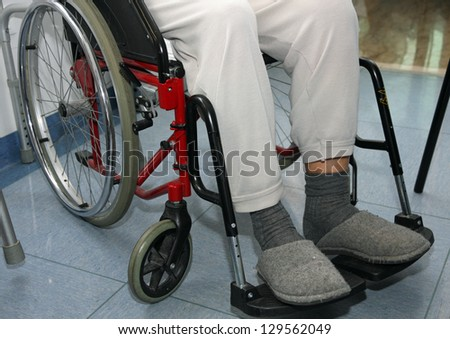 Elder patient with leg problems over the wheelchairs - stock photo