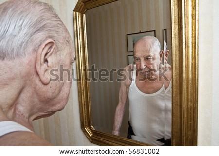 elder pensive at the mirror - stock photo