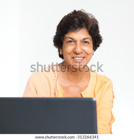 Elder people and modern technology concept. Portrait of a 50s Indian mature woman using internet at home. Indoor senior people living lifestyle. - stock photo