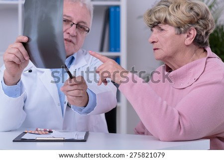Elder practitioner analyzing with patient chest x-ray - stock photo