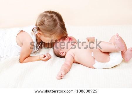 Elder sister kissing her newborn brother - stock photo