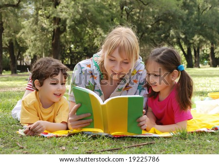 Elder sister reads to children of the book on a glade in park - stock photo