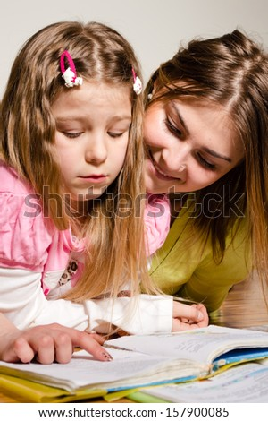 Elder sister teaches to read younger one at home on floor - stock photo