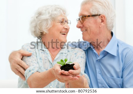 Elder smiling loving couple holding fresh green sprout, symbol of good bank investments for the retirement - stock photo