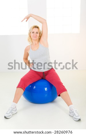 Elder woman dressed sportswear exercising with fitness ball. She's looking at camera. - stock photo