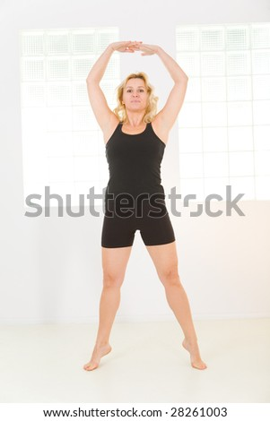 Elder woman dressed sportswear working out. She's looking at camera. Front view. - stock photo