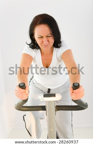 Elder woman exercising on  bike. She looks very tired. Front view.