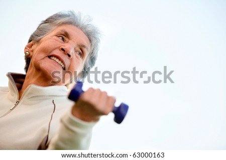 Elder woman exercising outdoors with free-weights and smiling - stock photo