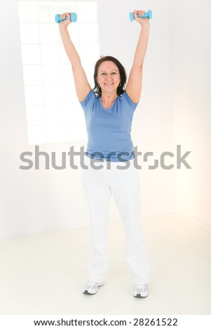 Elder woman exercising with dumbbell. She's smiling and looking at camera. Front viev. - stock photo
