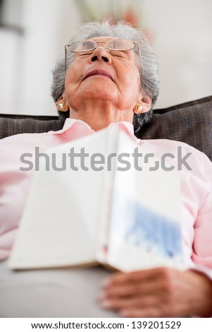 Elder woman falling asleep while reading a book - stock photo