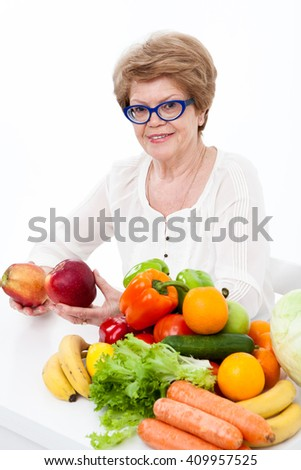 Elder woman holding two red apples in hands, sitting with fresh fruit and vegetables on table, white background - stock photo