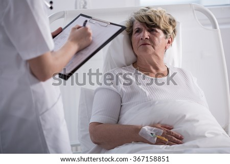 Elder woman in hospital bed talking to her doctor - stock photo