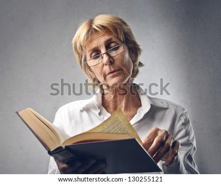 elder woman reading a book - stock photo