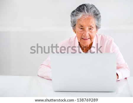 Elder woman using a laptop computer at home - stock photo