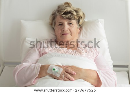 Elder woman with IV drip resting in bed - stock photo