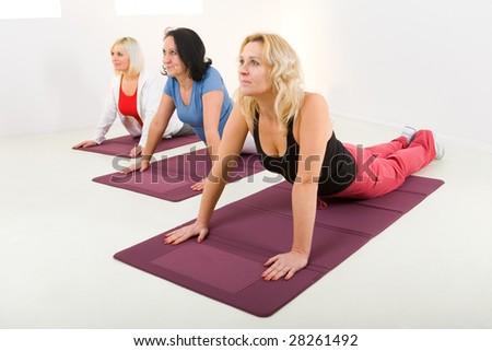 Elder women during exercising on mat. - stock photo