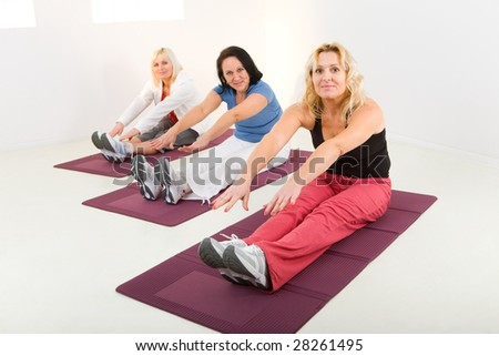 Elder women during exercising on mat. They're smiling and looking at camera. - stock photo