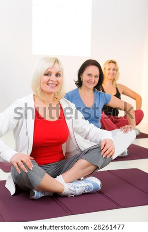 Elder women sitting cross-legged on mat and doing exercices. They're smiling and looking at camera. - stock photo