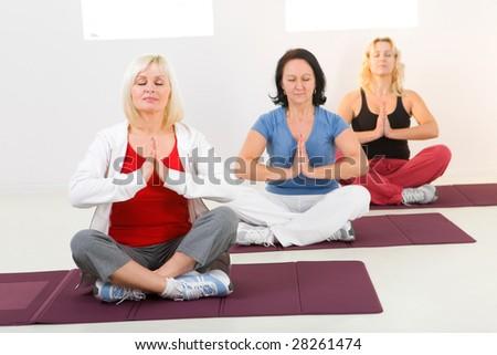 Elder women sitting cross-legged on mat and meditating - stock photo
