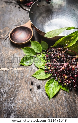 Elderberries for cooking with spoon and vintage pot on rustic wooden background - stock photo