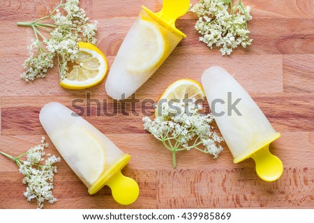 Elderberry ice lollies with lemon and flowers with flat lay photography. Horizontal image of fresh ice cream with natural ingredients like berries and lemon with wooden table background. - stock photo
