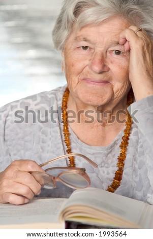 Elderly adorable woman with the book smiles