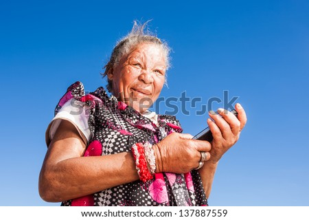 elderly african homeless lady playing around with a mobile phone - stock photo