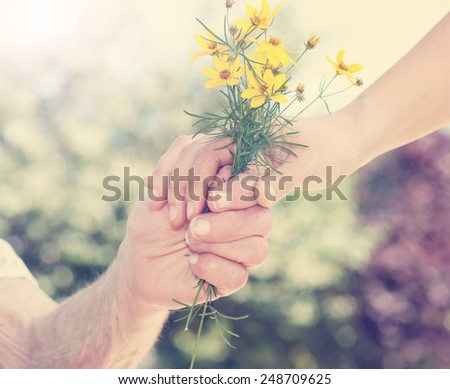 Elderly and young woman holding yellow flowers outside - stock photo