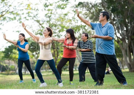 Elderly Asian people practicing Tai Chi together - stock photo