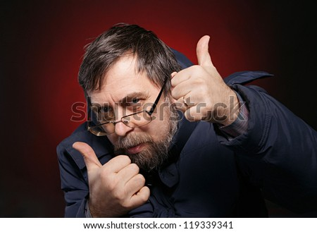 Elderly bearded man showing yes sign on a dark background
