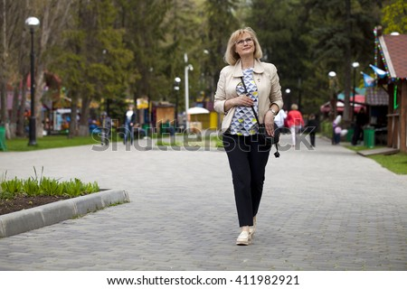 Elderly blonde woman walking in spring park - stock photo