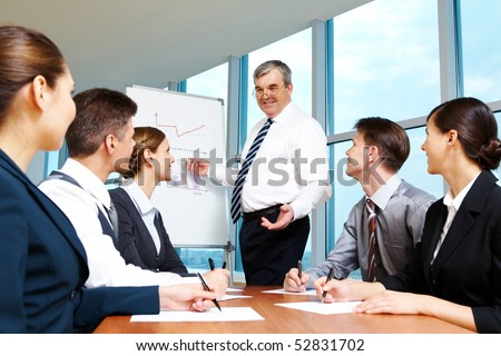 Elderly boss pointing at whiteboard and looking at managers during presentation - stock photo