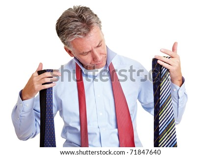 Elderly business man holding many different ties in his hands - stock photo