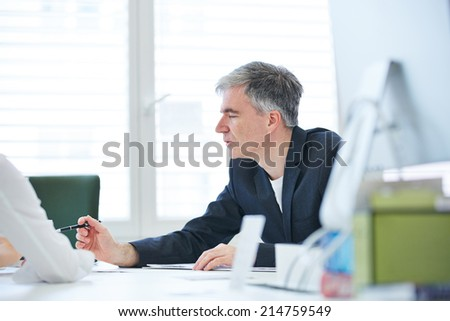 Elderly business man negotiating in meeting in the office - stock photo