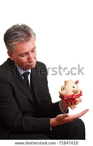 Elderly business man shaking an empty piggy bank - stock photo