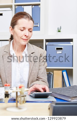 Elderly business woman doing tax audit in office with calculator