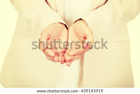Elderly business woman holding copyspace or something on open palms - stock photo